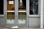 Two tennis racquets propped in the window of a closed pub in Wimbledon in London, Monday, June 29, 2020. The 2020 Wimbledon Tennis Championships, due to start Monday were cancelled due to the Coronavirus pandemic. (AP Photo/Kirsty Wigglesworth)
