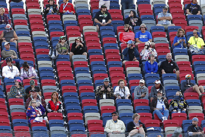 A limited number of fans social distance in the grandstands as they watch the NASCAR Xfinity Series auto race at Phoenix Raceway, Saturday, Nov. 7, 2020, in Avondale, Ariz. (AP Photo/Ralph Freso)