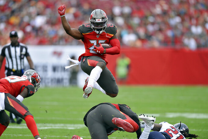 Tampa Bay Buccaneers running back Peyton Barber (25) hurdles a teammate on a run against the Houston Texans during the first half of an NFL football game Saturday, Dec. 21, 2019, in Tampa, Fla. (AP Photo/Jason Behnken)
