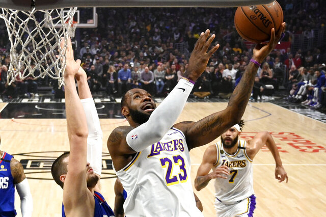 Los Angeles Lakers forward LeBron James, right, shoots as Los Angeles center Ivica Zubac defends during the first half of an NBA basketball game Sunday, March 8, 2020, in Los Angeles. (AP Photo/Mark J. Terrill)