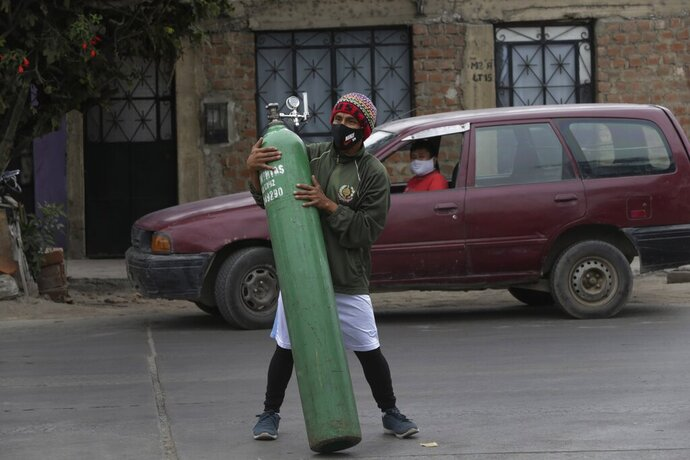 A man moves an empty oxygen cylinder in Callao, Peru, Wednesday 3, 2020. Long neglected hospitals in Peru and other parts of Latin America are reporting shortages of Oxygen as they confront the COVID-19 pandemic. (AP Photo/Martin Mejia)