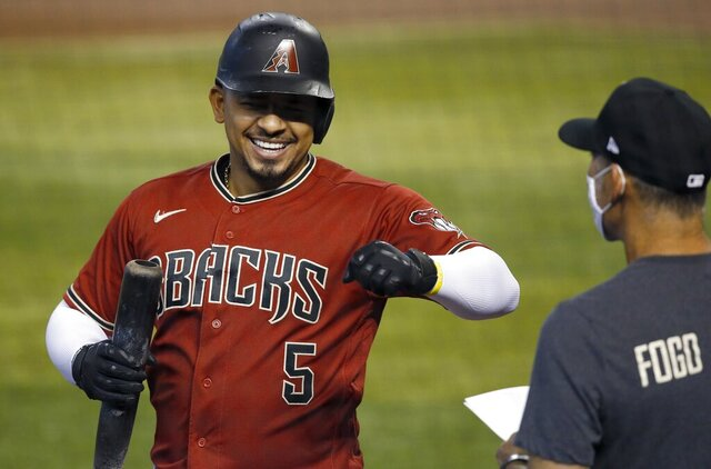 Arizona Diamondbacks' Eduardo Escobar (5) smiles as he celebrates his home run with manager Torey Lovullo, right, during a baseball training camp intrasquad scrimmage Sunday, July 12, 2020, in Phoenix. (AP Photo/Ross D. Franklin)