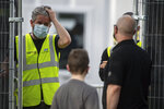 A man speaks with staff at the entrance to a coronavirus testing facility in Sutton Coldfield, England, Tuesday Sept. 13, 2020.  New measures are in place banning people from different homes from meeting together in some English cities, in response to a local rocketing coronavirus infection rate, although there is widespread criticism over the availability of testing facilities. (Jacob King/PA via AP)