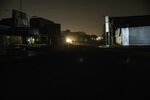 In this May 21, 2019 photo, a man walks in a dark downtown Maracaibo, Venezuela, during a black out. The situation is especially dire in Maracaibo, once known as Venezuela's Saudi Arabia for being at the hub of the country's now-decaying oil industry. Power plants put out a fraction of their potential, and the lights have flickered on and off since late-2017, when a major transmission line burned up. (AP Photo/Rodrigo Abd)