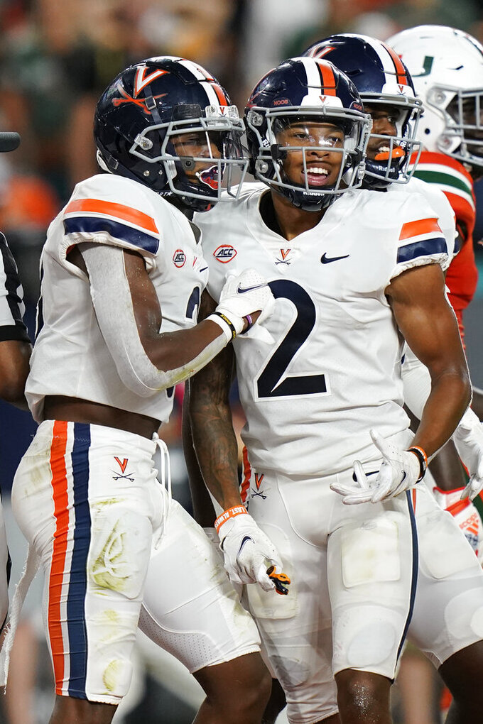 Virginia wide receiver Ra'Shaun Henry (2) congratulates wide receiver Dontayvion Wicks, after Wicks scored a touchdown during the second half of a NCAA college football game against Miami, Thursday, Sept. 30, 2021, in Miami Gardens, Fla. (AP Photo/Lynne Sladky)