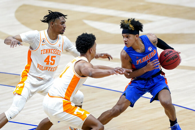 Florida's Tre Mann (1) is defended by Tennessee's Keon Johnson (45) and Jaden Springer (11) in the first half of an NCAA college basketball game in the Southeastern Conference Tournament Friday, March 12, 2021, in Nashville, Tenn. (AP Photo/Mark Humphrey)