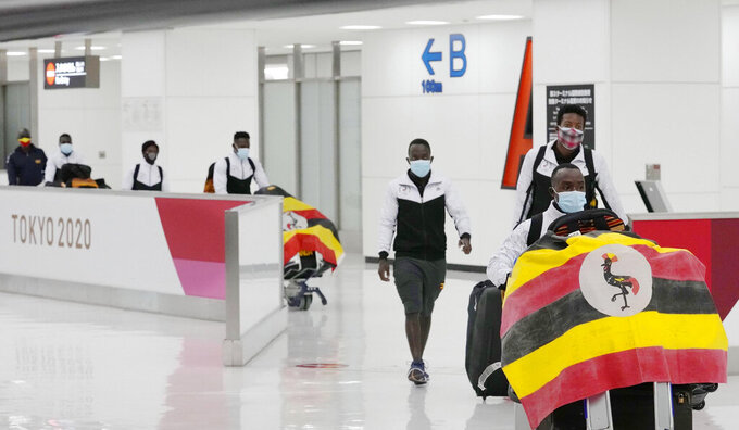 Members of Uganda's Olympic team leave Narita Airport in Narita, near Tokyo early Sunday June 20, 2021. A member of the team has tested positive for the coronavirus and was barred entry into Japan, in the first detected infection among arriving athletes for the Tokyo Games opening in five weeks. (Sadayuki Goto/Kyodo News via AP)