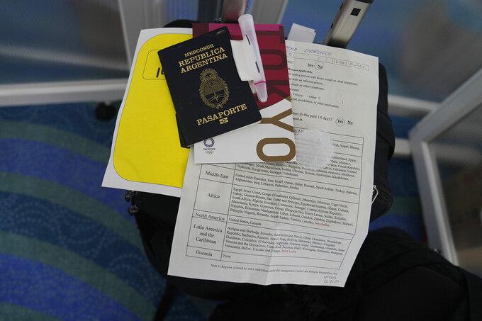 Associated Press photographer's Natacha Pisarenko documents rest on her suitcase at Haneda Airport in Tokyo upon arriving Monday, July 19, 2021. (AP Photo/Natacha Pisarenko)