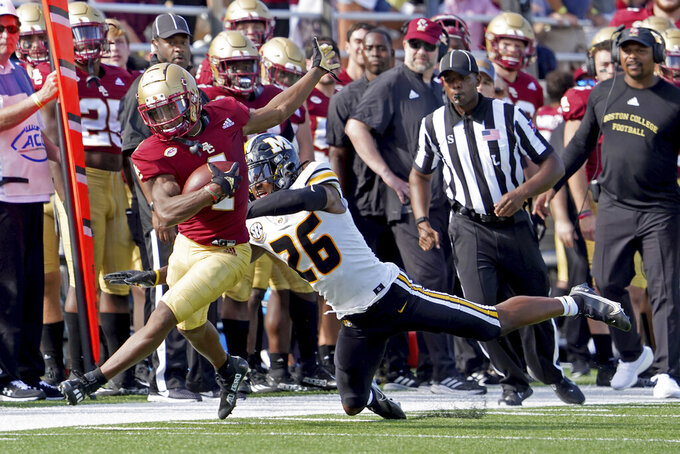 Boston College wide receiver Zay Flowers (4) rushes down the sideline ahead of Missouri defensive back Akayleb Evans (26) during the second half of an NCAA college football game, Saturday, Sept. 25, 2021, in Boston. (AP Photo/Mary Schwalm)