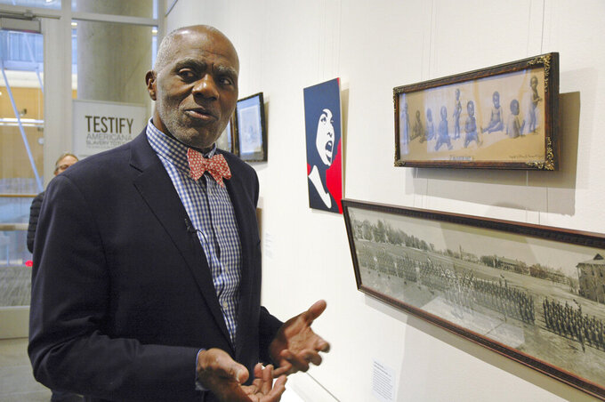 """FILE - In this Jan. 11, 2018 photo, Alan Page, NFL Hall of Famer and retired Minnesota Supreme Court justice, stands in Minneapolis, by a photo of black babies labeled """"Alligator Bait.""""  Page has counted art collection among his many life pursuits, and the former Vikings star has two of his prized pieces up for sale through a New York auction house, each valued at more than $200,000. (AP Photo/Steve Karnowski, File)"""