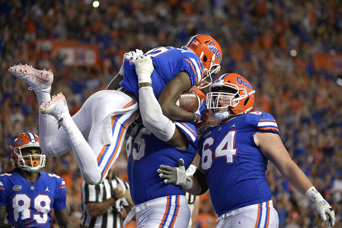 Florida wide receiver Van Jefferson (12) celebrates with wide receiver Tyrie Cleveland (89), offensive lineman Jawaan Taylor (65) and offensive lineman Tyler Jordan (64) after catching a pass in the end zone for a 6-yard touchdown during the first half of an NCAA college football game against the Charleston Southern Saturday, Sept. 1, 2018, in Gainesville, Fla. (AP Photo/Phelan M. Ebenhack)