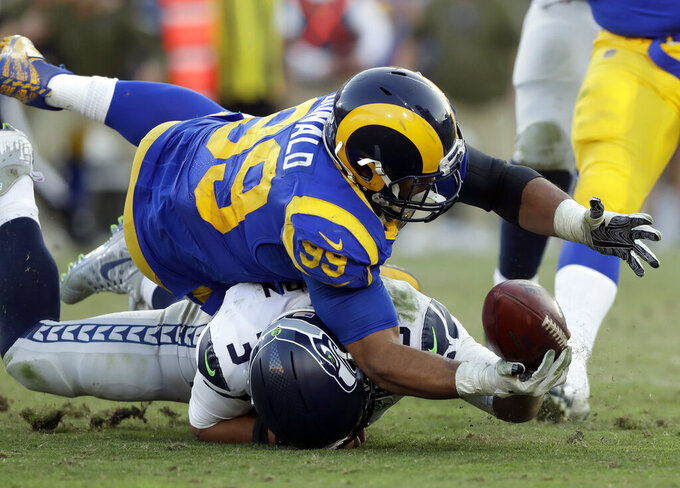 FILE - In this Nov. 11, 2018, file photo, Seattle Seahawks quarterback Russell Wilson (3) battles Los Angeles Rams defensive end Aaron Donald (93) for a ball Wilson lost on a fumble and returned for a touchdown by defensive end Dante Fowler during the second half in an NFL football game in Los Angeles. The Rams know they've got to pressure Tom Brady early and often to have a chance in the Super Bowl, and they've been assembling the tools for this job all year long. They signed Ndamukong Suh to a big free-agent deal, wrote a record-breaking contract for Aaron Donald and acquired edge rusher Dante Fowler from Jacksonville down the stretch.  (AP Photo/Alex Gallardo, File)