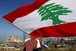 A man holds the Lebanese flag, as he looks at the scene of Tuesday's explosion that hit the seaport of Beirut, Lebanon, Friday, Aug. 7, 2020. Rescue teams were still searching the rubble of Beirut's port for bodies on Friday, nearly three days after a massive explosion sent a wave of destruction through Lebanon's capital. (AP Photo/Hussein Malla)