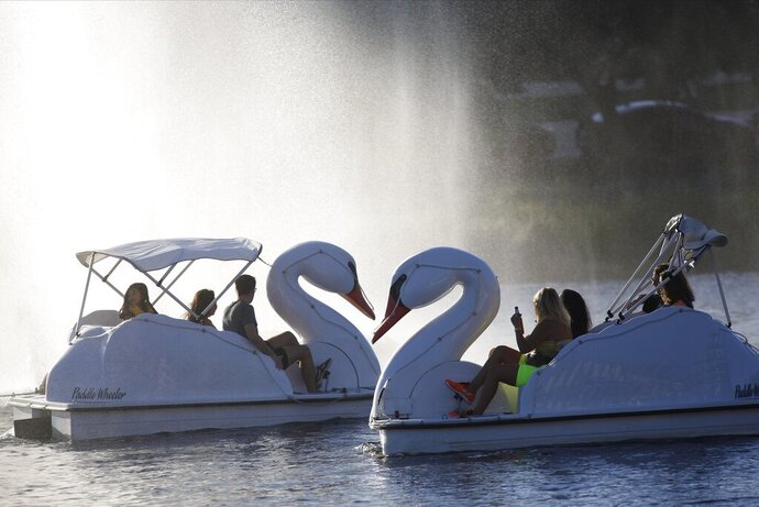 Visitors cool off under a stream of water as they ride paddle wheelers in Echo Park Lake in Los Angeles Saturday, Sept. 14, 2019. Southern California is baking under a weekend heat wave that's dropping humidity levels and raising the risk of wildfires. Residents are urged to limit strenuous outdoor activity. (AP Photo/Damian Dovarganes)