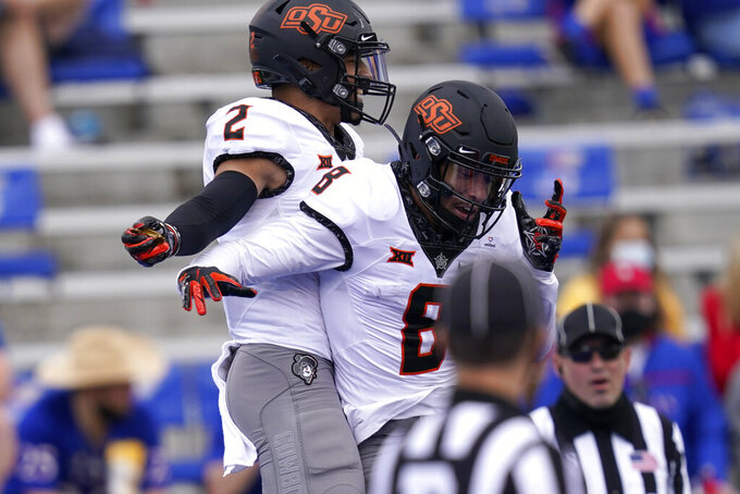 Oklahoma State wide receivers Tylan Wallace (2) and Braydon Johnson (8) celebrate a touchdown during the first half of an NCAA college football game against Kansas in Lawrence, Kan., Saturday, Oct. 3, 2020. (AP Photo/Orlin Wagner)