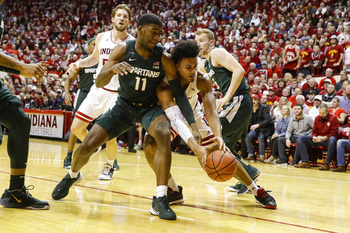 Michigan State forward Aaron Henry (11) and Indiana forward Justin Smith (3) go for a loose ball in the first half of an NCAA college basketball game in Bloomington, Ind., Thursday, Jan. 23, 2020. (AP Photo/Darron Cummings)