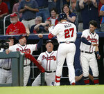 Atlanta Braves' rookie Austin Riley (27) is rested by bench coach Walt Weiss, left, manager Brian Snitker and shortstop Dansby Swanson, right after hitting home run in the fourth inning of a baseball game against the St. Louis Cardinals Wednesday, May 15, 2019, in Atlanta. It was Riley's first Major League hit. (AP Photo/John Bazemore)