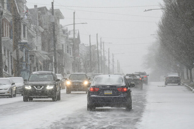 Traffic moves slowly along W. Market Street in Pottsville, Pa., as the snow begins to fall with Winter Storm Gail on Wednesday, Dec. 16, 2020. (Jacqueline Dormer/Republican-Herald via AP)