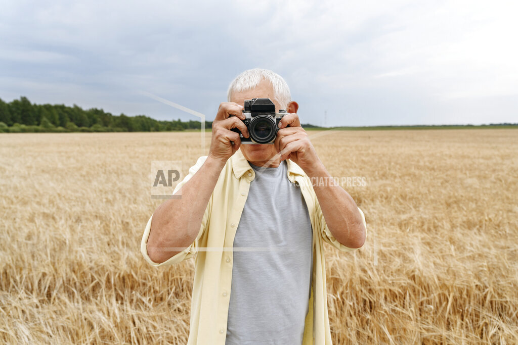 Man photographing through camera on wheat field