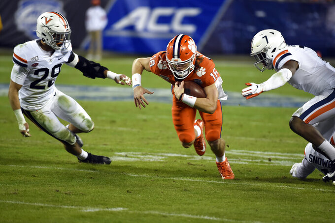 Clemson quarterback Trevor Lawrence (16) runs between Virginia safety Joey Blount (29) and Virginia safety Chris Moore (7) during the first half of the Atlantic Coast Conference championship NCAA college football game in Charlotte, N.C., Saturday, Dec. 7, 2019. (AP Photo/Mike McCarn)