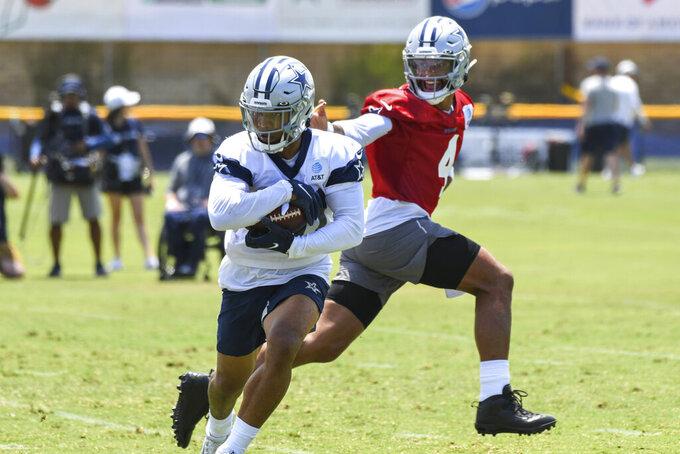 Dallas Cowboys running back Tony Pollard takes a handoff from quarterback Dak Prescott during the NFL football team's training camp in Oxnard, Calif., Thursday, July 22, 2021. (AP Photo/Michael Owen Baker)