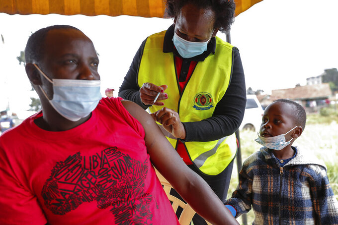 A Kenyan man receives a dose of AstraZeneca coronavirus vaccine donated by Britain, as his son watches, at the Makongeni Estate in Nairobi, Kenya Saturday, Aug. 14, 2021. In late June, the international system for sharing coronavirus vaccines sent about 530,000 doses to Britain – more than double the amount sent that month to the entire continent of Africa. It was the latest example of how a system that was supposed to guarantee low and middle-income countries vaccines is failing, leaving them at the mercy of haphazard donations from rich countries.(AP Photo/Brian Inganga)