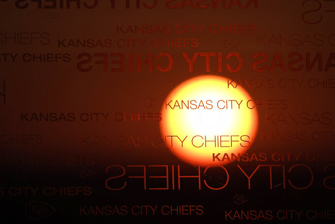 The sunset is shown through glass at Arrowhead Stadium before an NFL football game between the Kansas City Chiefs and Denver Broncos in Kansas City, Mo., Sunday, Dec. 6, 2020. (AP Photo/Charlie Riedel)