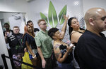 FILE - In this July 1, 2017, file photo, people wait in line at the Essence cannabis dispensary in Las Vegas. Nevada is set to pioneer a law to prevent job-seekers from being immediately rejected for work based on a positive marijuana test. (AP Photo/John Locher, File)