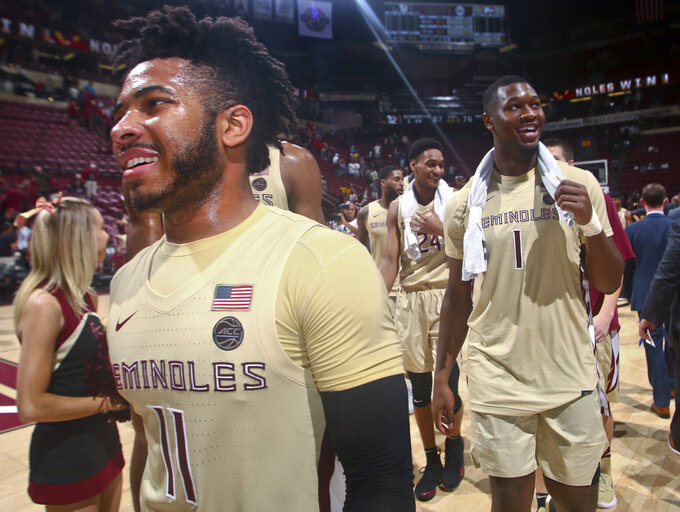 Florida State guard David Nichols (11), forward RaiQuan Gray (1) and guard Devin Vassell (24) smile after the team's NCAA college basketball game against Winthrop in Tallahassee, Fla., Tuesday, Jan. 1, 2019. Florida State won 87-76. (AP Photo/Phil Sears)