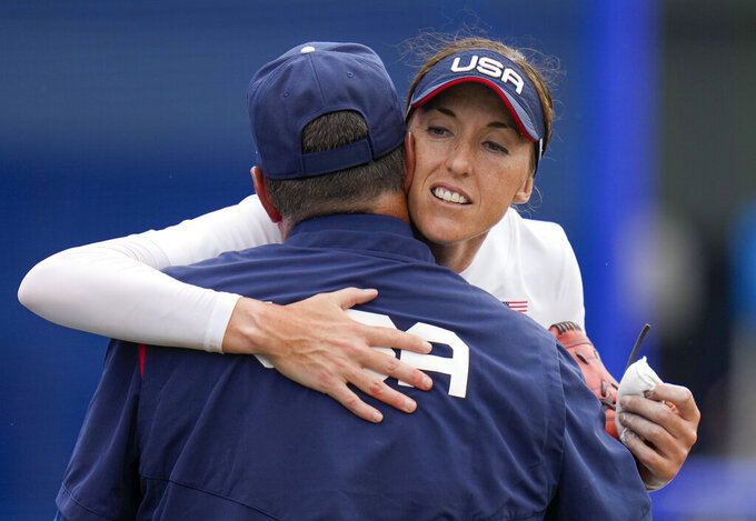 United States head coach Ken Eriksen embraces Monica Abbott after defeating Canada in their softball game at the 2020 Summer Olympics, Thursday, July 22, 2021, in Fukushima , Japan. (AP Photo/Jae C. Hong)