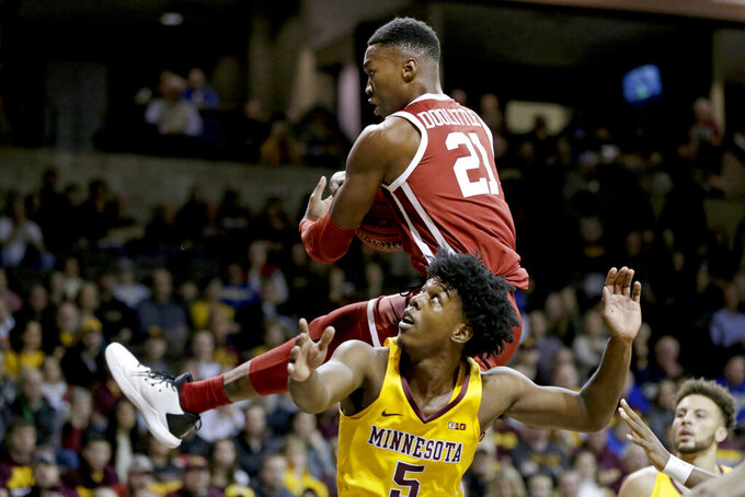 Oklahoma's Kristian Doolittle (21) grabs a rebound over Minnesota's Marcus Carr (5) during the first half of an NCAA college basketball game in Sioux Falls, S.D., Saturday, Nov. 9, 2019. (AP Photo/Nati Harnik)