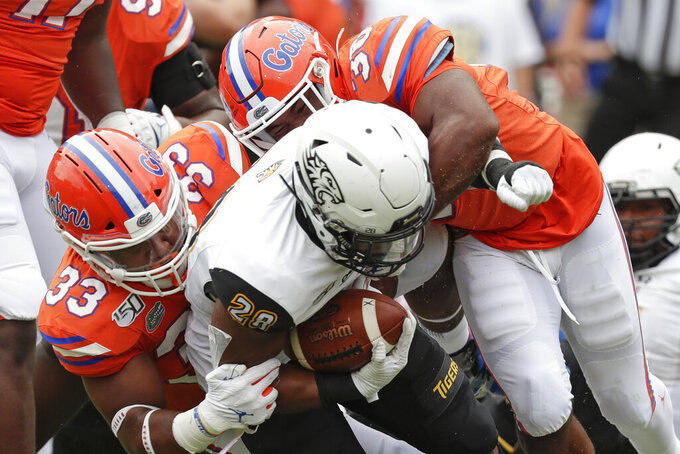 Towson running back Yeedee Thaenrat, center is tackled after a short gain by Florida linebacker David Reese II (33) and defensive back Amari Burney during the first half of an NCAA college football game, Saturday, Sept. 28, 2019, in Gainesville, Fla. (AP Photo/John Raoux)