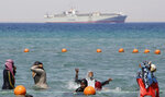 FILE - In this Sunday, Aug. 9, 2015 file photo, a ship crosses the Gulf of Suez towards the Red Sea as holiday-makers swim in Suez, 127 kilometers (79 miles) east of Cairo, Egypt. The Suez Canal, which connects the Red Sea to the Mediterranean Sea, revolutionized maritime travel by creating a direct shipping route between the East and the West. But as Egypt marks the 150th anniversary of its opening, marine biologists are bemoaning one of the famed waterway's lesser known legacies, the invasion of hundreds of non-native species that have driven the native marine life toward extinction and altered the delicate Mediterranean ecosystem with potentially devastating consequences. (AP Photo/Amr Nabil, File)