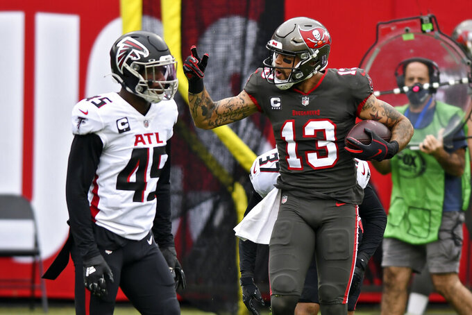 Tampa Bay Buccaneers wide receiver Mike Evans (13) reacts after catching a pass in front of Atlanta Falcons linebacker Deion Jones (45) during the first half of an NFL football game Sunday, Jan. 3, 2021, in Tampa, Fla. Evans' reception put him over the 1,000 yard mark for the season. (AP Photo/Jason Behnken)
