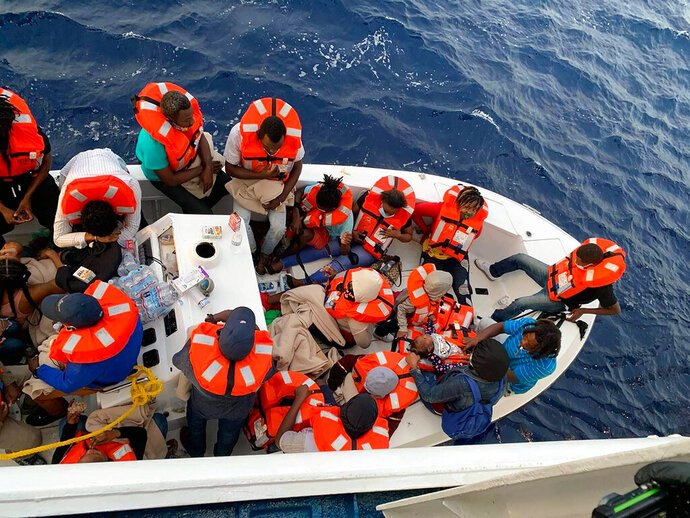 This photo provided by Carnival Cruise Line shows people after being rescued by a Carnival Cruise Line ship off the Florida coast, the cruise line reported Saturday, Oct. 17, 2020. It was not immediately clear why the smaller boat came under distress, but its passengers were taken on board the Carnival Sensation when the boat started taking on water. (Carnival Cruise Line  via AP)