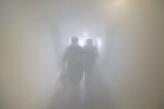 A couple wearing protective face masks walk through a decontamination chamber as a preventive measure against the spread of the new coronavirus, before entering a store in Caracas, Venezuela, Saturday, July 25, 2020. (AP Photo/Matias Delacroix)