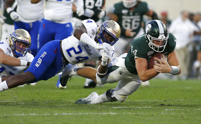 Michigan State quarterback Brian Lewerke, right, dives for a first down against Tulsa's Treyvon Reeves (24) and Cooper Edmiston, left, during the second quarter of an NCAA college football game, Friday, Aug. 30, 2019, in East Lansing, Mich. (AP Photo/Al Goldis)