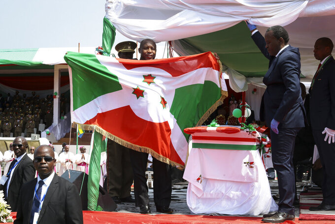Burundi's President Evariste Ndayishimiye holds the national flag after his inauguration in Gitega, Burundi Thursday, June 18, 2020. President Evariste Ndayishimiye took power two months early after the abrupt death of his predecessor Pierre Nkurunziza. (AP Photo/Berthier Mugiraneza)