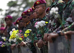 Indonesian marines hold flowers given by student protesters during a rally outside the parliament in Jakarta, Indonesia, Tuesday, Oct. 1, 2019. Indonesia's Parliament was sworn in Tuesday for a new session that comes amid spasmodic violent anti-government protests. (AP Photo/Dita Alangkara)