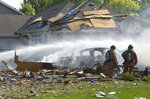 FILE - In this Aug. 14, 2017 file photo, firefighters walk through rubble following a house explosion in Lincoln, Neb. A man fatally injured in a natural gas explosion at the house in Lincoln intentionally caused the blast so he could kill his wife, Lincoln police said Thursday, Oct. 11, 2018. (Amber Baesler /Lincoln Journal Star via AP, File)