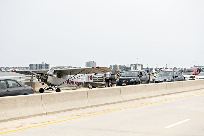 Emergency responders talk with Landon Lucas, 18, a pilot flying for Paramount Air Service, after he made an emergency landing on the Route 52 causeway connecting Ocean City and Somers Point, N.J. on Monday, July 19, 2021. No injuries were reported. (Matthew Strabuk/The Press of Atlantic City via AP)