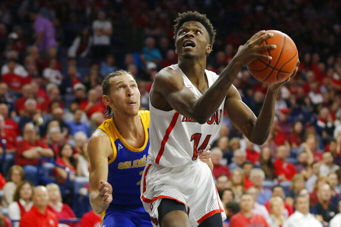 Arizona guard Devonaire Doutrive (14) looks to the basket as San Jose State guard Brae Ivey defends during the second half of an NCAA college basketball game Thursday, Nov. 14, 2019, in Tucson, Ariz. Arizona won 87-39. (AP Photo/Rick Scuteri)