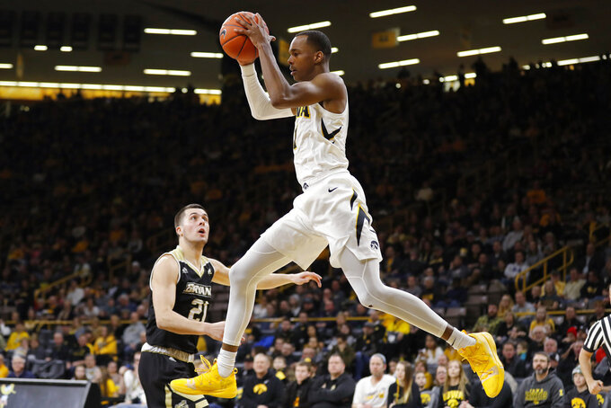 Iowa guard Maishe Dailey catches a pass over Bryant guard Tanner Johnson (21) during the first half of an NCAA college basketball game Saturday, Dec. 29, 2018, in Iowa City, Iowa. (AP Photo/Charlie Neibergall)