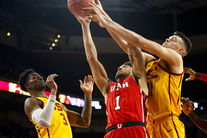 Utah forward Timmy Allen, center, reaches for a rebound next to Southern California forward Nick Rakocevic, right, during the second half of an NCAA college basketball game Thursday, Jan. 30, 2020 in Los Angeles. (AP Photo/Kyusung Gong)