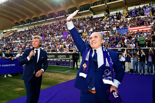 FILE - In this Friday, June 7, 2019 filer, Rocco Commisso, right, is flanked by former soccer star Giancarlo Antognoni as he waves to supporters at the Artemio Franchi stadium in Florence, Italy. Less than six months into his tenure as Fiorentina owner and president, Rocco Commisso is already starting to grapple with Italy's infamous bureaucracy as he attempts to build a new stadium for the club. First, Commisso's plan to overhaul the existing Stadio Artemio Franchi was rejected by the city committee that protects monuments. Now he is awaiting approval to build a new ground, perhaps near the city's airport. (Claudio Giovannini/ANSA via AP, File )