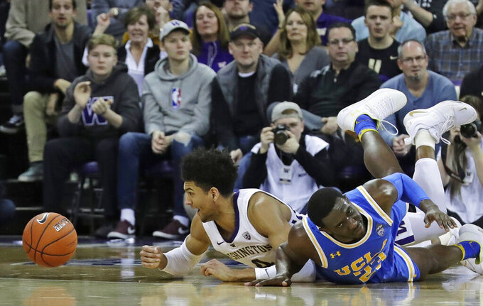 Washington guard Matisse Thybulle, left, reacts after battling with UCLA guard Prince Ali, right, for a loose ball during the second half of an NCAA college basketball game Saturday, Feb. 2, 2019, in Seattle. Washington won 69-55. (AP Photo/Ted S. Warren)