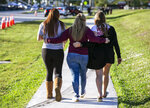 Marjory Stoneman Douglas High School student Sophia Rothenberg, from left to right, her mother Cheryl Rothenberg and sister, Emma Rothenberg, walk together after visiting a a memorial marking the one-year anniversary of a mass shooting at the school in Parkland, Fla., on Thursday, Feb. 14, 2019. (Al Diaz/Miami Herald via AP)