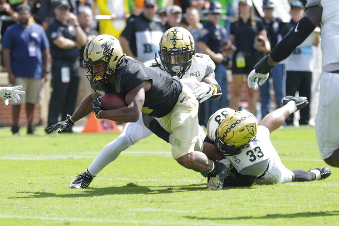 Purdue wide receiver Rondale Moore (4) is tackled by Vanderbilt defensive back Randall Haynie (4) and safety Dashaun Jerkins (33) during the first half of an NCAA college football game in West Lafayette, Ind., Saturday, Sept. 7, 2019. (AP Photo/Michael Conroy)