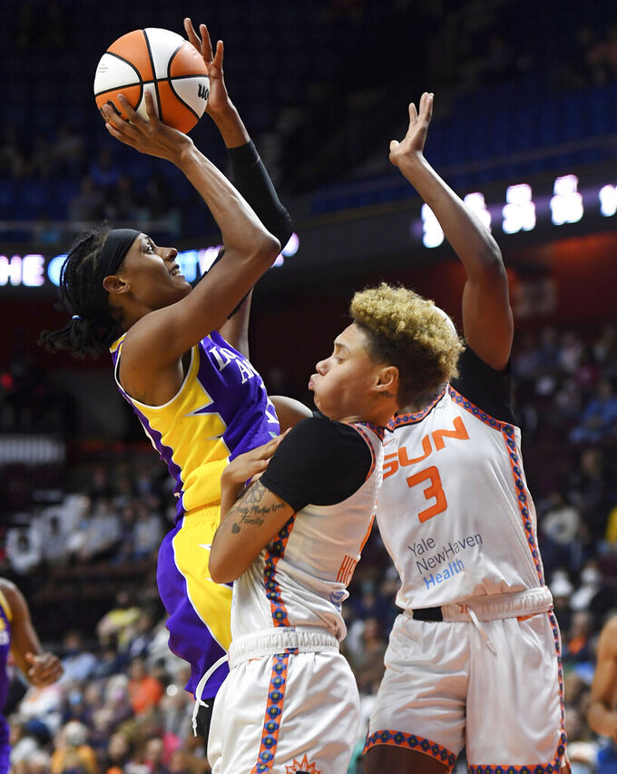 Los Angeles Sparks guard Brittney Sykes shoots over Connecticut Sun guard Natisha Hiedeman and forward Kaila Charles (3) during a WNBA basketball game Saturday, Aug. 28, 2021, in Uncasville, Conn. (Sean D. Elliot/The Day via AP)