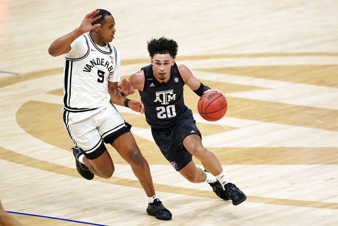 Texas A&M's Andre Gordon (20) drives against Vanderbilt's D.J. Harvey (5) in the second half of an NCAA college basketball game in the Southeastern Conference Tournament Wednesday, March 10, 2021, in Nashville, Tenn. (AP Photo/Mark Humphrey)
